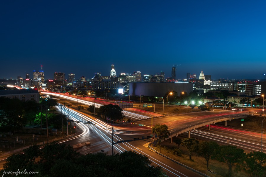 Austin Texas skyline at night with car light trails on IH35
