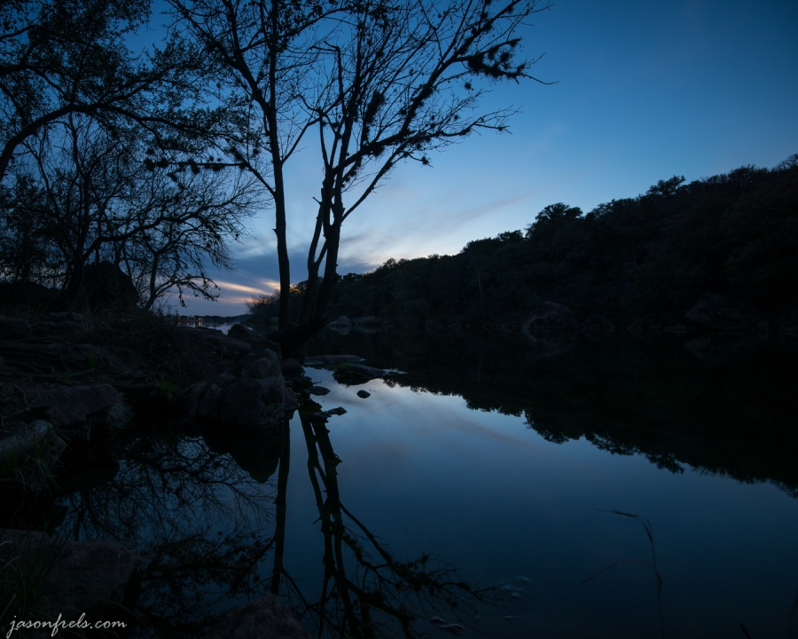 Tree silhouetted against sky and lake at blue hour at Inks Lake State Park Texas