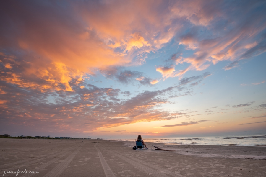 A woman watches Sunrise on the Beach